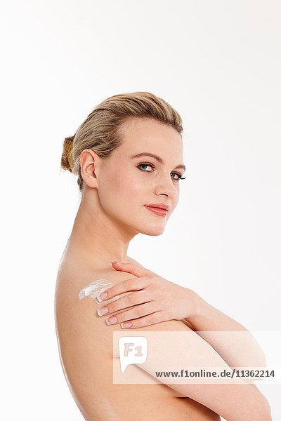 Studioporträt einer schönen nackten blonden jungen Frau  die Feuchtigkeitscreme auf die Schulter aufträgt