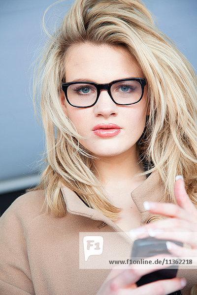 Porträt einer blonden jungen Frau mit Brille und Smartphone