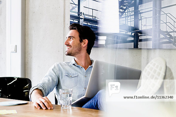 Business man in office feet up on desk  using laptop looking away smiling