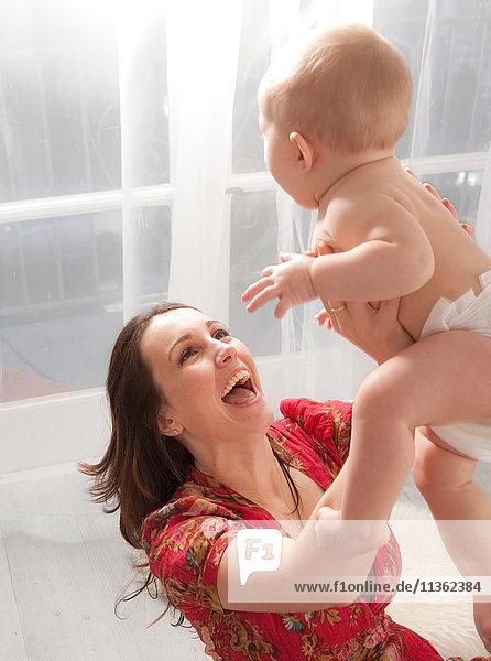Mutter hebt Baby-Tochter in die Luft  lachend
