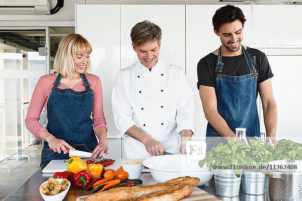 Koch und Ehepaar in der Küche beim Gemüseschneiden