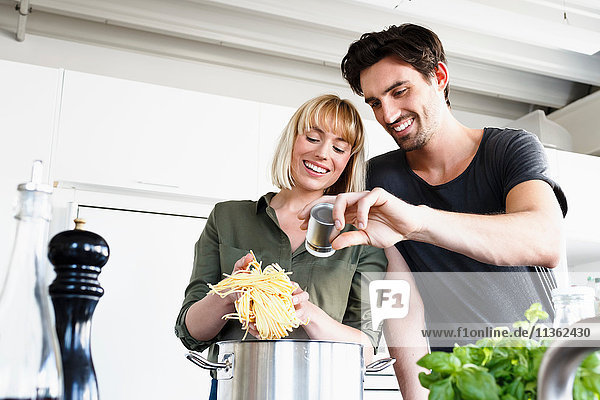 Couple in kitchen cooking pasta