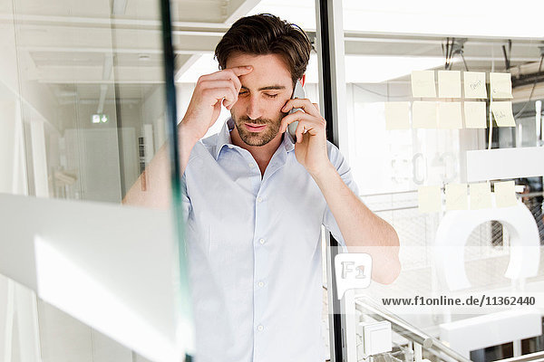 Businessman in office using mobile phone