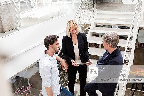 Business people with digital tablet talking on stairway