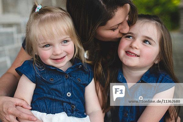 Girls sitting on mothers lap smiling