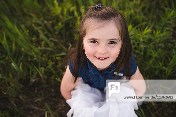 Girl sitting on grass looking up at camera smiling