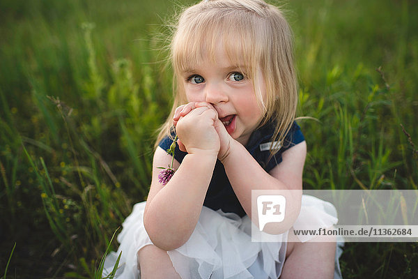 Portrait of girl sitting on grass looking at camera