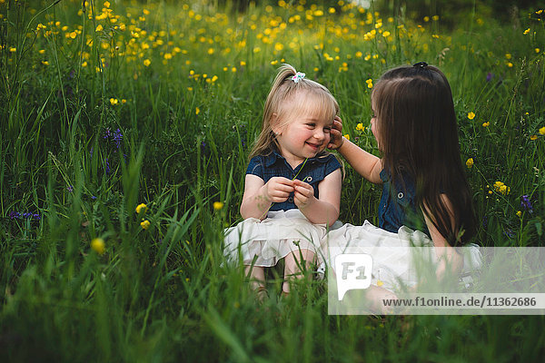 Girls sitting in wildflower meadow face to face smiling