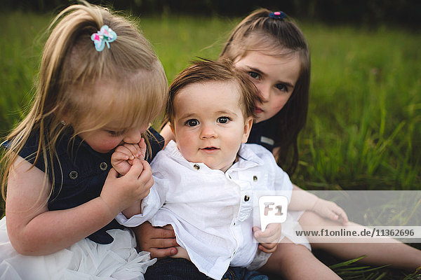 Sisters hugging baby brother