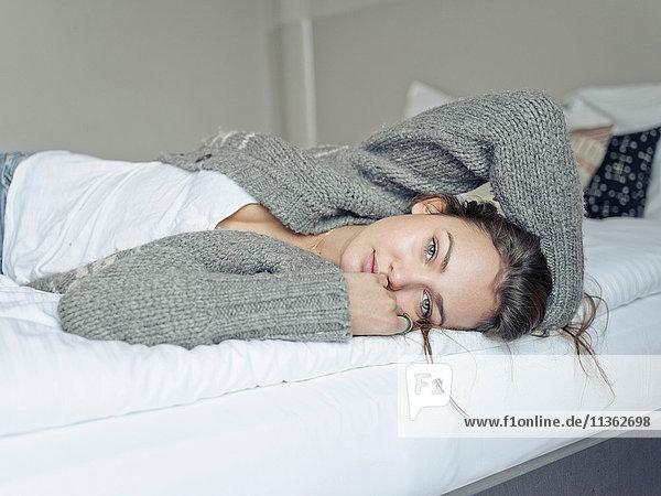 Frau liegt auf Bett und schaut in die Kamera