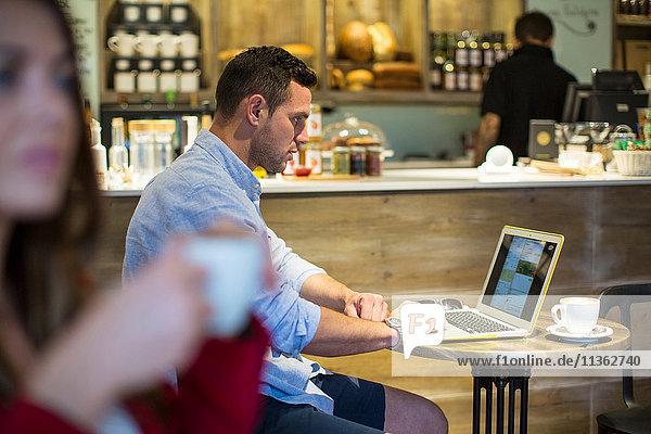 Mann sitzt im Café und liest Laptop