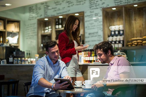 Männliche Freunde sitzen im Café und schauen auf das digitale Tablet