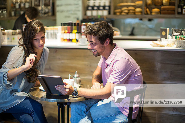 Junges Paar im Café betrachtet digitales Tablett