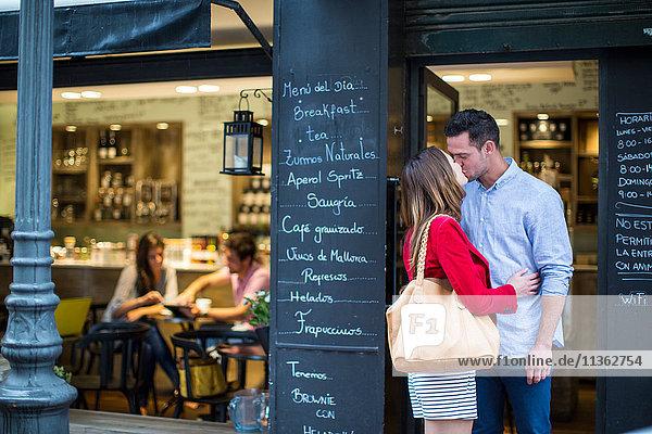 Romantisches Paar küsst sich vor einem Café