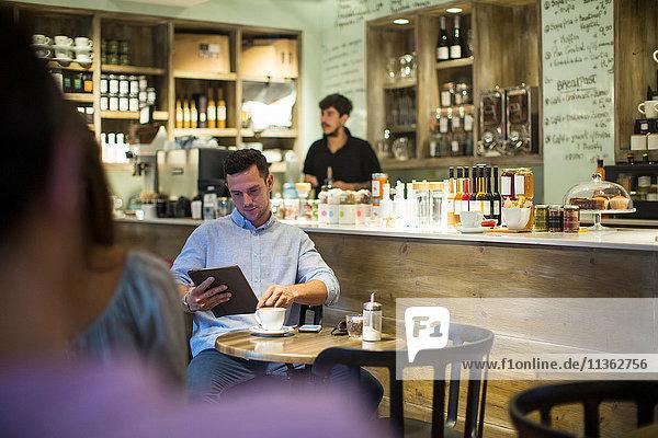 Mann sitzt im Café und blättert am digitalen Tablet