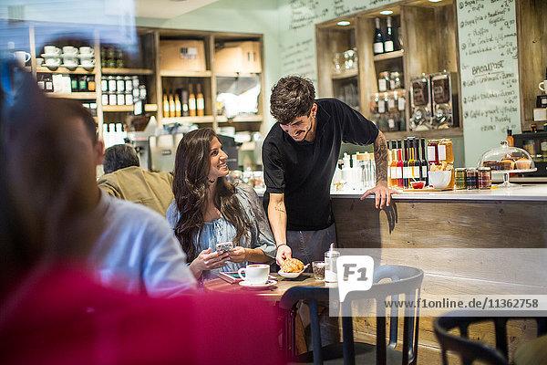 Barista bedient junge Kundin im Café