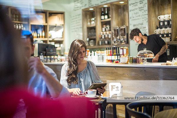 Junge Frau betrachtet digitales Tablet im Café