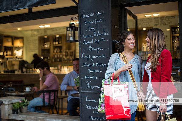 Zwei junge Freundinnen vor einem Café mit Einkaufstaschen