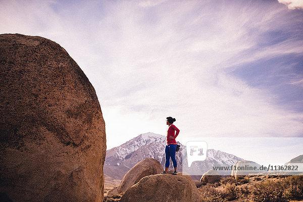 Frau steht auf der Spitze eines Felsens und schaut weg  Buttermilk Boulders  Bishop  Kalifornien  USA