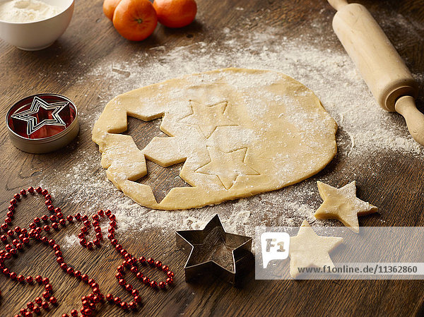 Table with christmas star biscuit dough and rolling pin