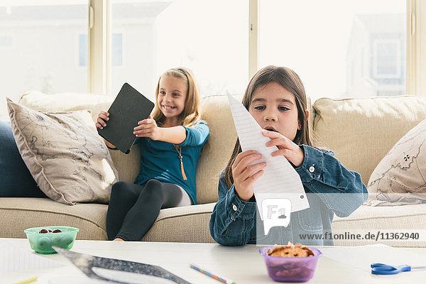Mädchen zu Hause mit digitalem Tablet  Papierflugzeug machen