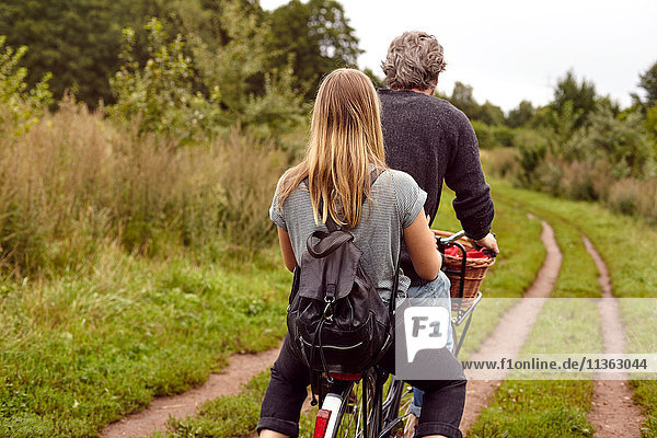 Rückansicht eines Fahrrad fahrenden Paares auf ländlichem Feldweg