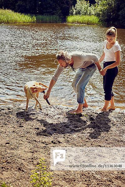 Pärchen spielt mit Hund am Flussufer