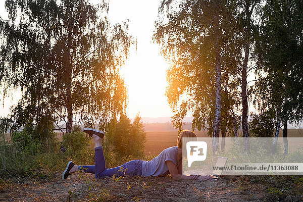 Am Spielfeldrand liegende Frau mit Laptop beim Sonnenuntergang