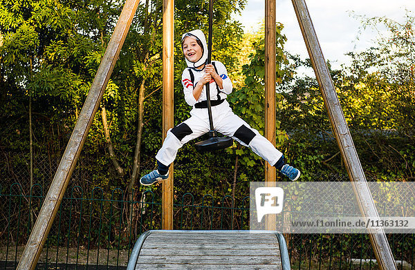 Porträt eines Jungen in Astronautenkostüm  der auf einer Seilrutsche auf dem Spielplatz reitet