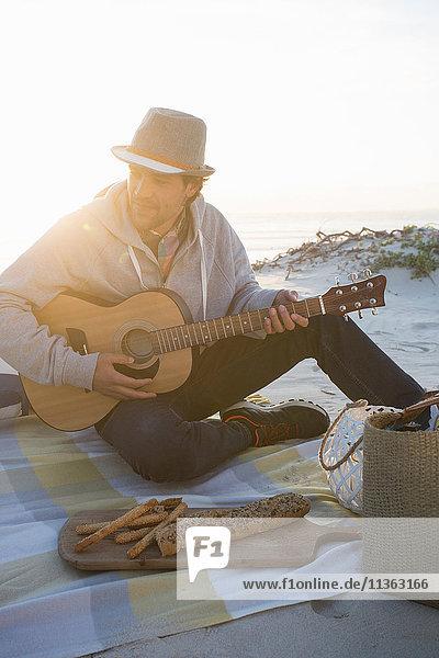 Junger Mann spielt Gitarre auf einer Picknickdecke am Strand  Kapstadt  Westkap  Südafrika