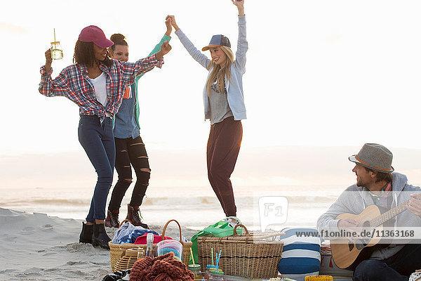 Junger Mann spielt Gitarre und Freundinnen tanzen am Strand  Kapstadt  Western Cape  Südafrika