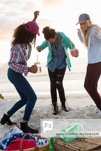 Drei junge Freundinnen tanzen beim Strandpicknick  Kapstadt  Western Cape  Südafrika