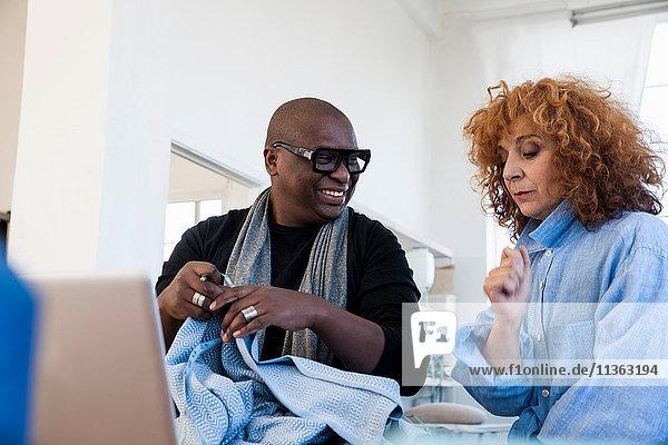 Männliche und weibliche Modedesigner untersuchen Material im Designstudio