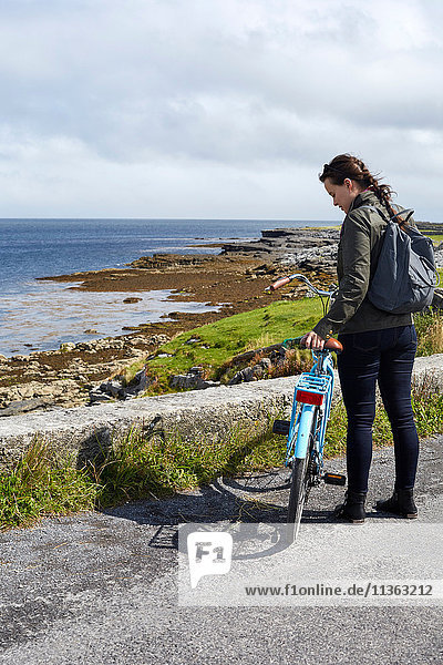 Young woman standing with bicycle beside sea wall  Inishmore  Ireland