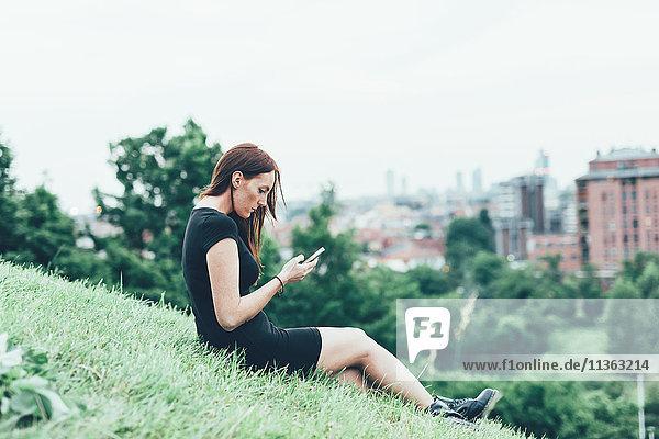 Junge Frau sitzt am Hang und liest Smartphone-Texte über der Stadt.