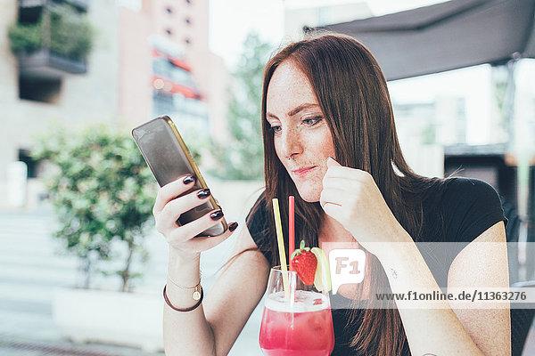 Junge Frau auf dem Bürgersteig Cafe lesen Smartphone-Texte
