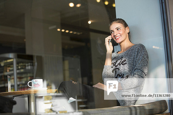 Young woman sitting in cafe  using smartphone  smiling