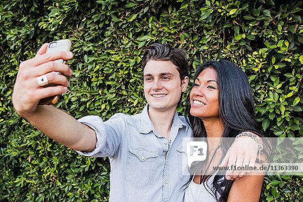 Junges Paar im Freien  Selbsthilfe  Smartphone