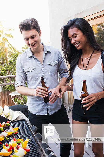 Young couple outdoors  holding beer bottles  cooking food on barbecue
