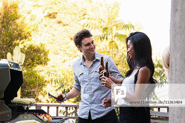 Junges Paar im Freien  Bierflaschen haltend  Essen auf dem Grill kochend