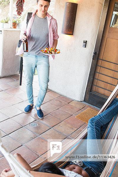 Junge Frau entspannt sich auf Veranda in Hängematte  junger Mann bringt Essen und Trinken