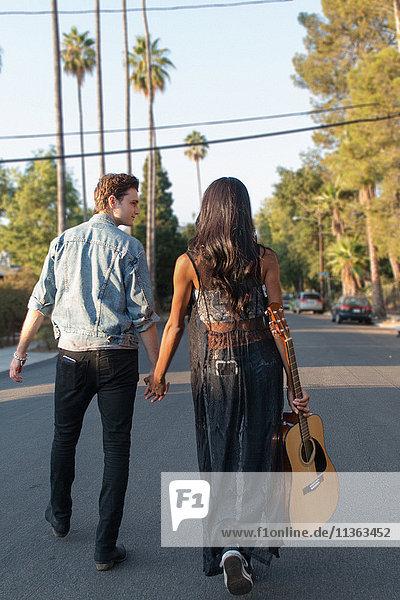 Junges Paar beim Spaziergang im Freien  junge Frau mit Gitarre in der Hand  Rückansicht