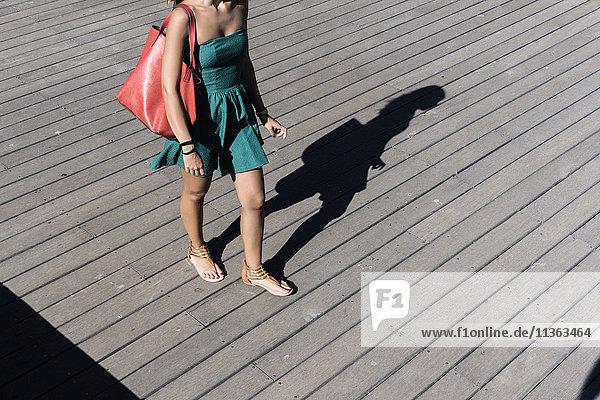 Ausschnitt einer Frau im Sonnenkleid mit Handtasche