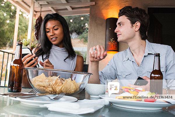 Young couple sitting on veranda  enjoying meal