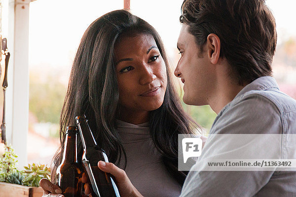 Young couple sitting on veranda  holding beer bottles