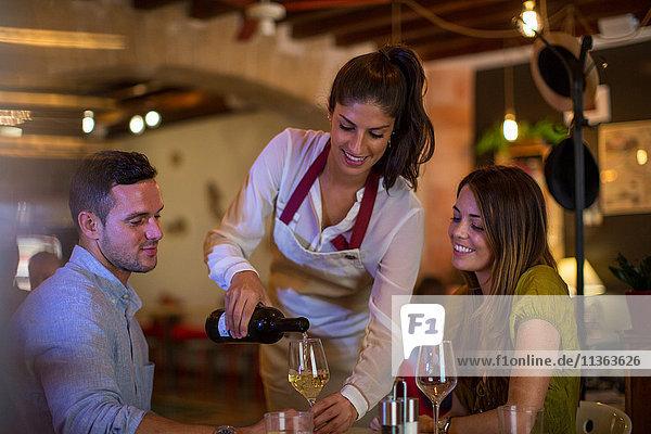 Kellnerin  die Kunden im Restaurant Wein serviert