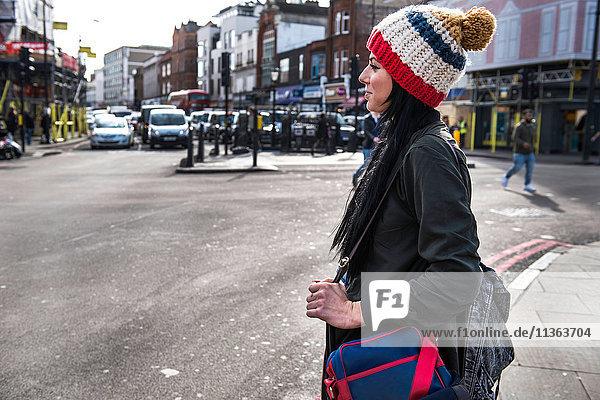 Junge Frau überquert Stadtstraße