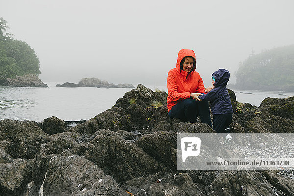 Mother and son on rocks  Vancouver Island  British Columbia  Canada