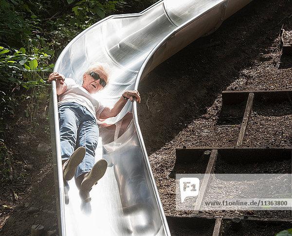 Frau rutscht eine Spielplatzrutsche hinunter