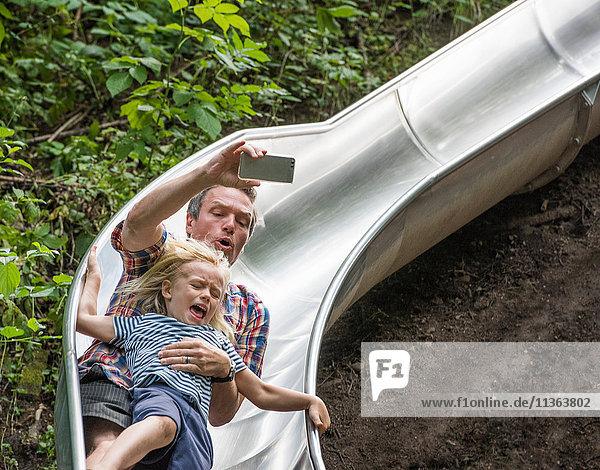 Vater und Sohn rutschen mit Smartphone nach unten